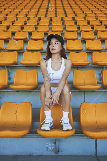 Confident Asian athletic woman in sportswear sitting on stadium seat while resting after workout and looking away