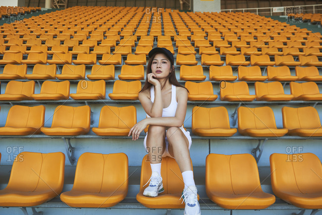 Confident Asian athletic woman in sportswear sitting on stadium seat while resting after workout and looking at camera
