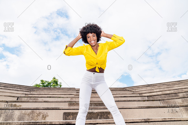From below optimistic black woman in trendy clothes smiling for camera and dancing with raised arms on sunny day in park