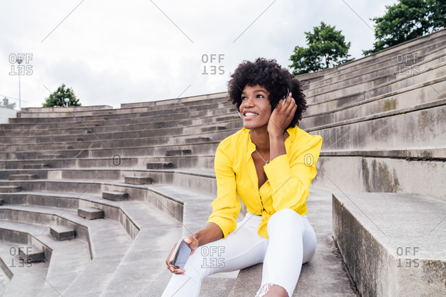 Smiling African American female with Afro hairstyle sitting on stairs in city and using a cellphone