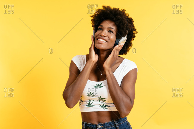 Glad African American female smiling and listening to music in headphones with closed eyes against yellow background