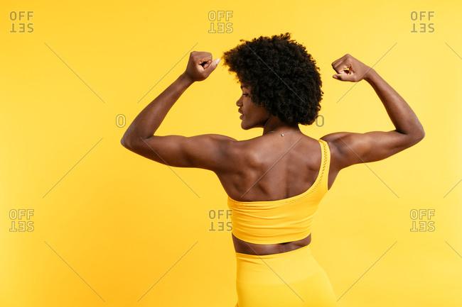 Black female in yellow sportswear posing y against yellow background