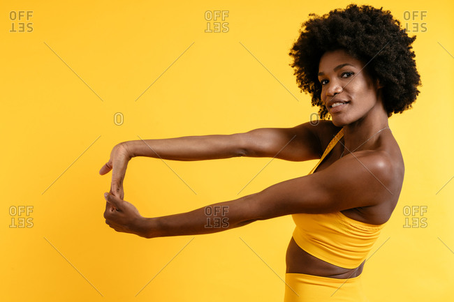 Black female in yellow sportswear posing and looking away against yellow background