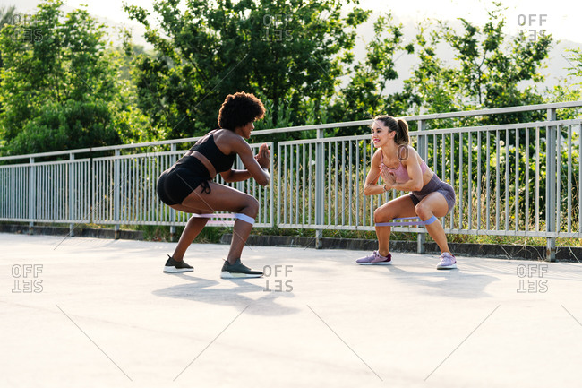 Full body of determined young multiethnic sportswomen doing squat exercise with resistance band during fitness workout in park in summer day