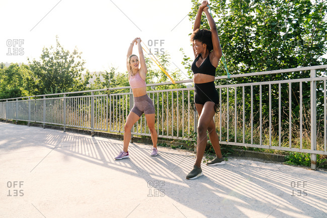 Low angle of diverse female athletes in sportswear doing exercises with resistance bands near metal railing on terrace in summer