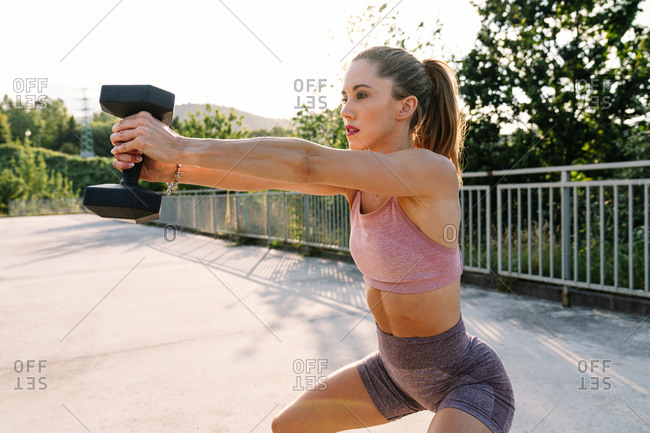 Fit female with strong body pumping muscles with dumbbell during training in summer
