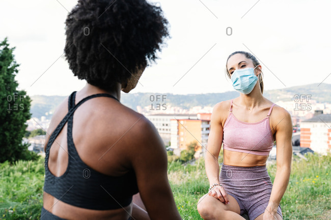 Young fit female friends in activewear and protective masks sitting on wooden fence and chatting while having break during outdoor training in summer day