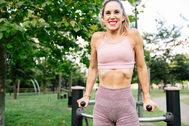 Positive young slim female in sportswear doing exercises on sports equipment during fitness workout in summer park
