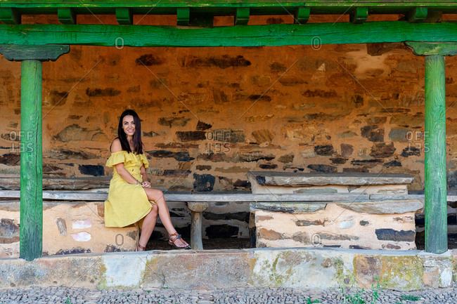 Satisfied female in summer dress sitting on old wooden bench near weathered building during stroll around old town