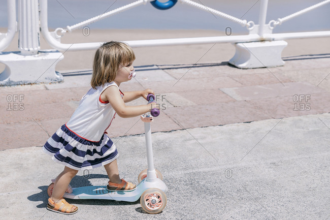 Side view of cheerful little girl riding kick scooter and having fun on promenade near sea in sunny day