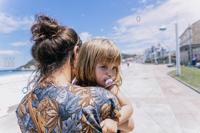 Back view of mother with cute little daughter standing at seafront and enjoying sunny weather during vacation