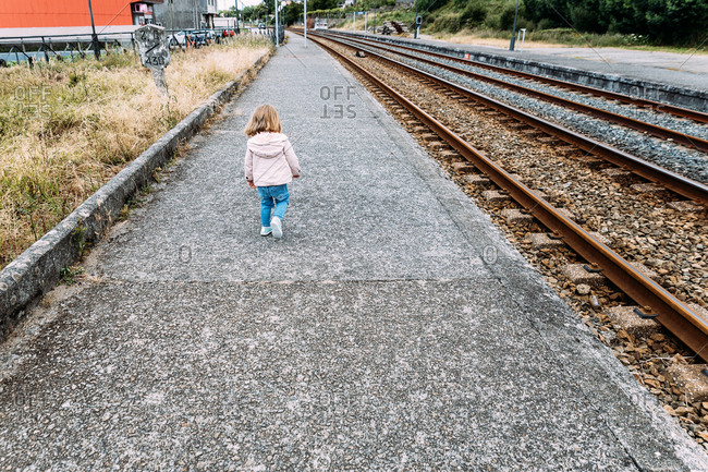 Back view of adorable little girl in casual wear walking at railway station while waiting for train