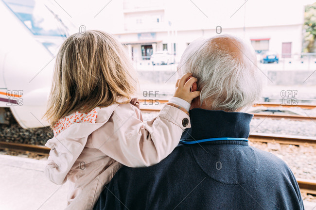 Back view of anonymous grandfather hugging cute granddaughter at railway station near train