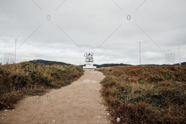 Narrow pathway running through grassy hill and leading to lighthouse tower against gray overcast sky in Spain