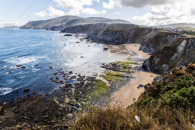 From above picturesque scenery of sea bay with blue waving water surrounded by rocky cliffs with small sandy beach in sunny summer day with cloudy sky in Spain