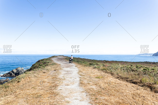 Back view of distant unrecognizable female with baby pram walking along coastal headland and admiring seascape