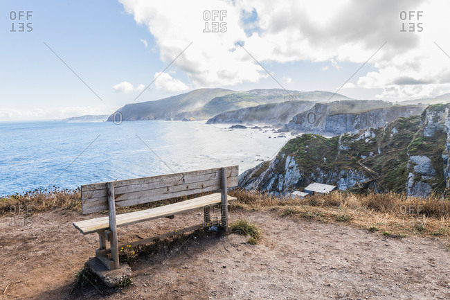 Old wooden bench located on cliff near rippling water of sea bay with rocky mountains on shore in sunny day with cloudy sky in Spain