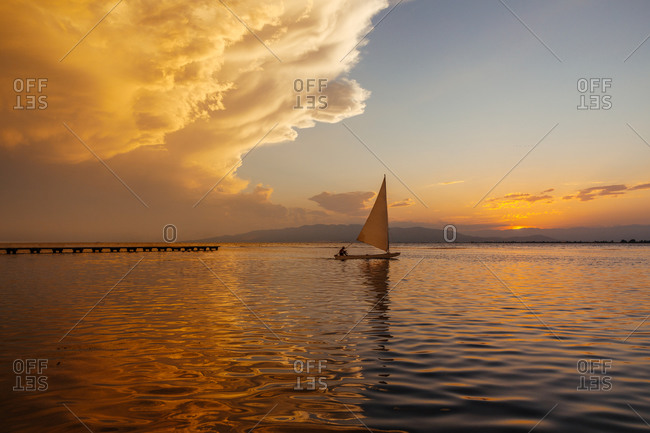 Little sailing boat in the sea at sunset with the sun and clouds in the background. Sailing on a summer adventure in the Mediterranean sea