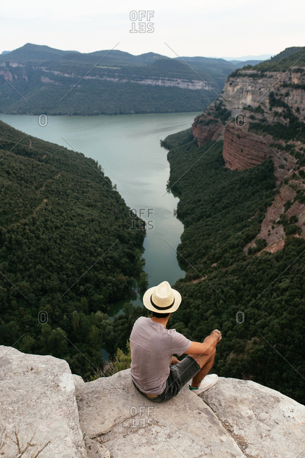 High angle back view of male tourist sitting in stone and admiring breathtaking scenery of river between mountains