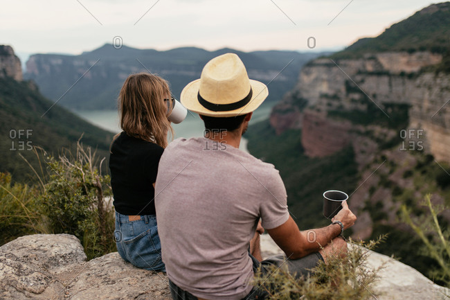 Back view of unrecognizable traveling couple sitting on hill and drinking hot coffee while enjoying majestic view of highland landscape