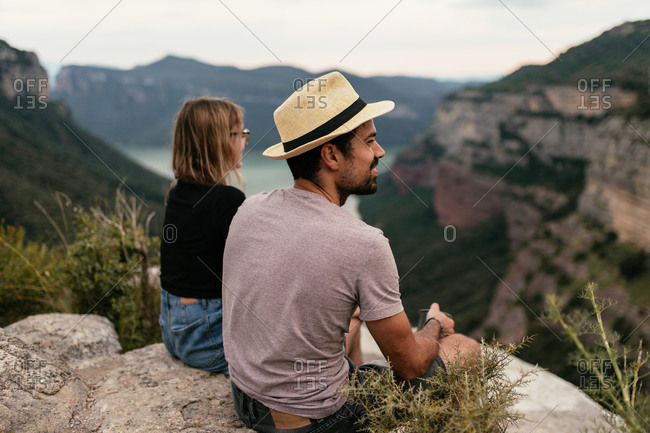 Back view of traveling couple sitting on hill and drinking hot coffee while enjoying majestic view of highland landscape