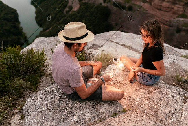 From above of traveling couple with illuminated garland relaxing on stone on background of mountainous landscape while enjoying holiday in summer