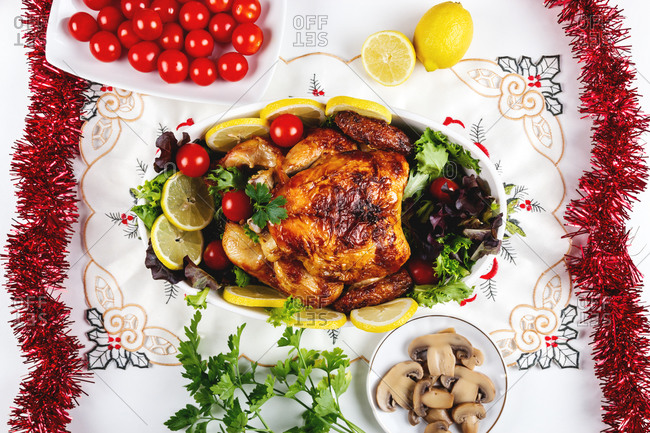 Top view of festive table served with baked chicken with various vegetables and placed near plates and fruits