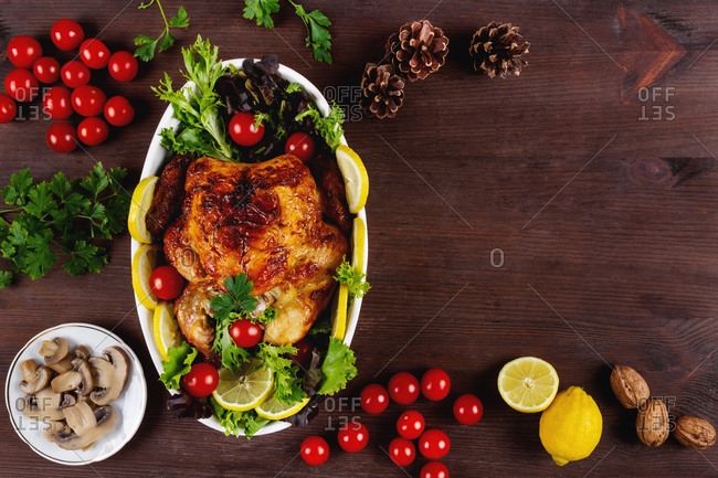 Top view of delicious roasted chicken with fresh tomatoes and parsley placed on table with lemon and mushrooms
