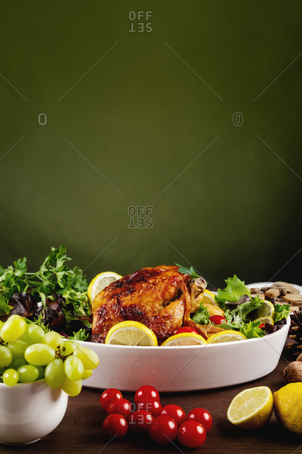 Delicious roasted chicken with fresh tomatoes and parsley placed on table with lemon and mushrooms