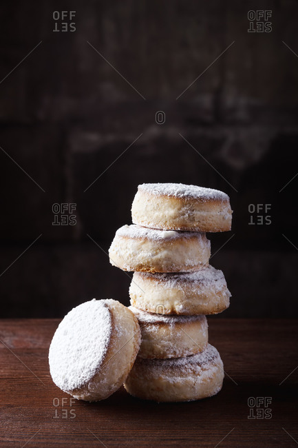 Pile of homemade delicious curd buns with sugar powder placed on wooden table in kitchen