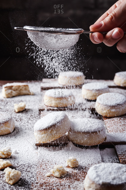Unrecognizable chef standing at table and sprinkling freshly baked buns with powdered sugar