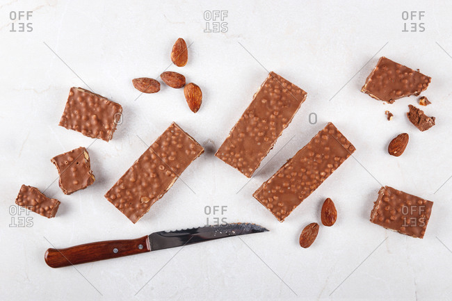 Sweet chocolate bars and almonds scattered on table and placed near knife in kitchen