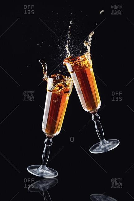 Crystal clinking glasses with splashing alcohol beverage on black background in modern studio