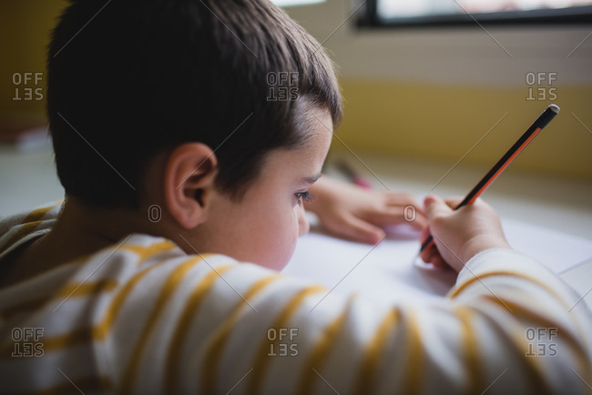 Side view of crop cute kid sitting at wooden table and drawing with pencil on paper while relaxing at weekend at home