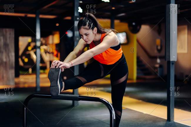 Full body young sporty female in fitness outfit performing stretching exercise near metal bar while warming up during training in gym