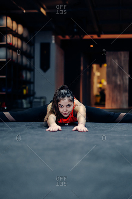 Full body young sporty female in fitness outfit performing stretching exercise on the floor while warming up during training in gym