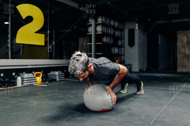 Full length of strong determined athletic male doing plank exercise with medicine ball during workout in gym