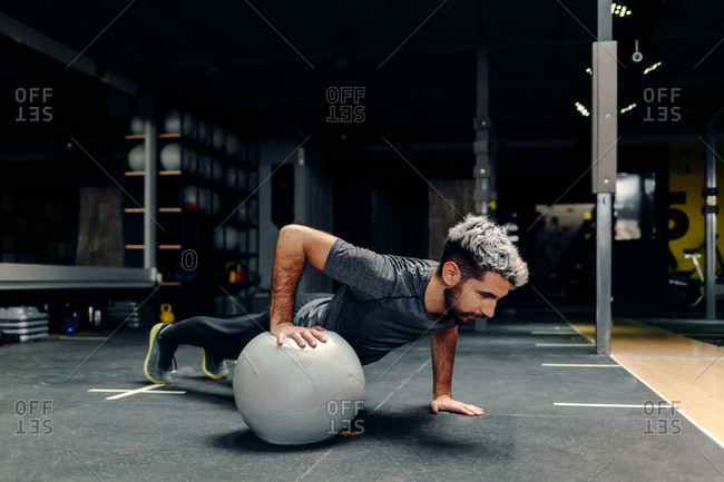 Full length of strong determined athletic male doing plank exercise using one hand with medicine ball during workout in gym