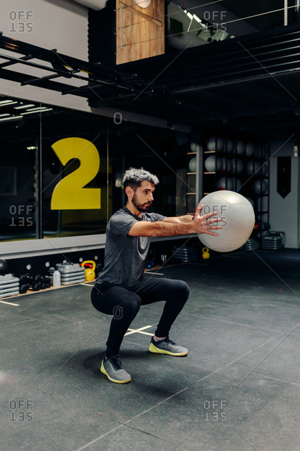 Full length of strong determined athletic male doing squats with medicine ball during workout in gym