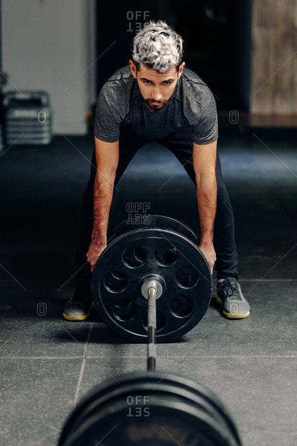 Male athlete in sportswear putting heavy plates on barbell while preparing for weightlifting workout in gym