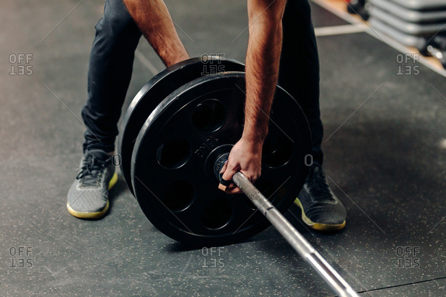 Crop anonymous male athlete in sportswear putting heavy plates on barbell while preparing for weightlifting workout in gym