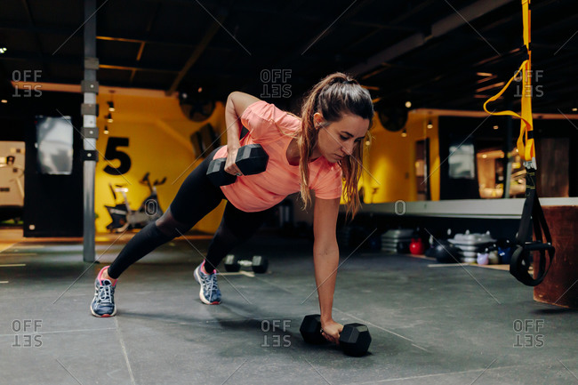 Full body focused young fit female performing push up exercise with dumbbells during intense workout in contemporary sports center with modern equipment