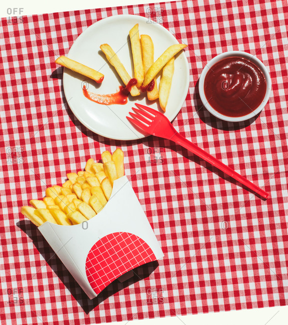 From above french fries packet near plate with potatoes soaked in ketchup