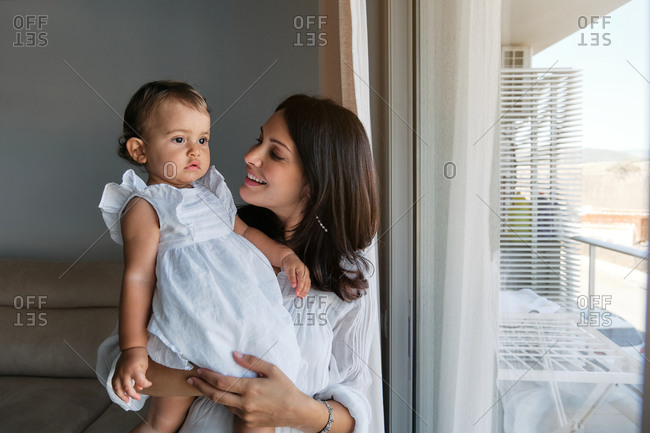 Mother with a little girl in white dress in her arms in front of a window looking at her with tender expression in a house