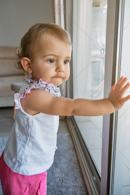 Vertical photo of a little girl standing with her hands on a window looking at the outside with distracted expression in a house