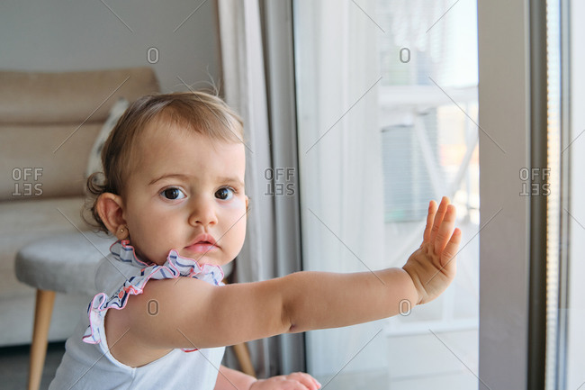 Little girl standing with her hands on a window looking at a side with distracted expression in a house
