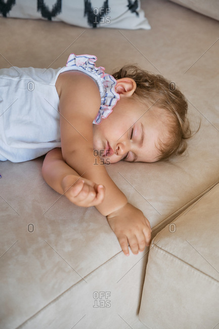 Little girl sleeping on the couch of a house