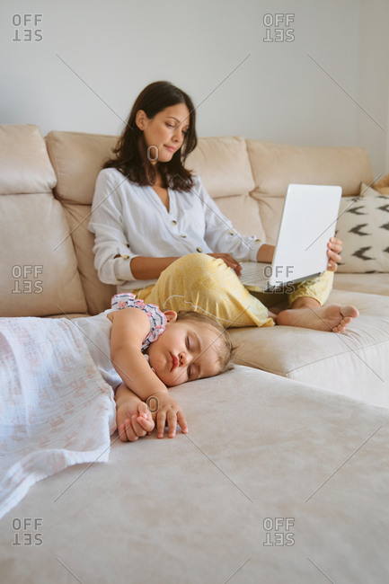 Little girl sleeping on the sofa while her mother works with a laptop next to her