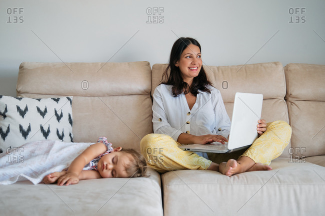 Woman working on the sofa with happy expression with the laptop while a toddler is sleeping on a side at home