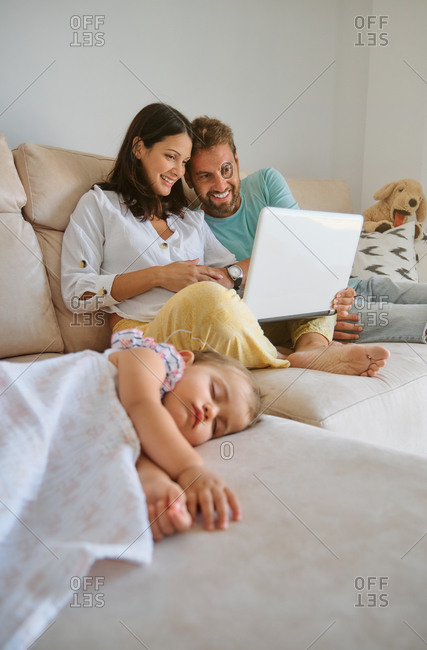 Little girl sleeping on the couch while a couple looks at the laptop next to her at home